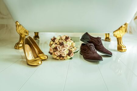 trotters: Wedding background. Vintage wedding background with bouquet, golden female and brown male shoes near the white bath. Stock Photo