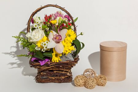 Different beautiful flowers in the basket, round beige box and handmade eggs close up on the white background.