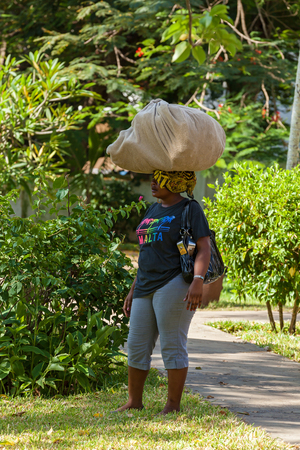 difficult lives: Mombasa, Kenya - 07 January 2013  the African woman stands with a sack on a head Editorial