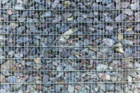 gabion mesh: fence from the pieces of granite and metallic grates