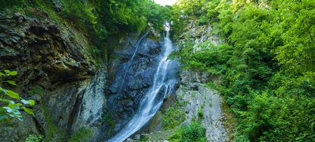 waterfall in mountain forest under blue sky. Sights of Georgia