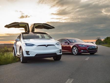Oekraïne, Kiev, 14 september 2017: Elektrische auto Tesla op een landweg, foto Tesla in de avond bij zonsondergang