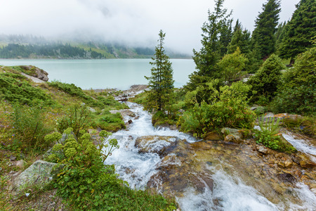 The mountain stream flows into the big Almaty lake. large reservoir of fresh drinking water