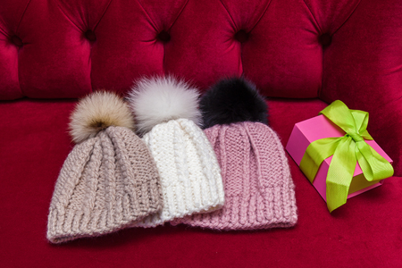 91751226 - winter knitted hats with a fur ball lay on the red couch. knitted  hats and a New Years gift 48322169224c
