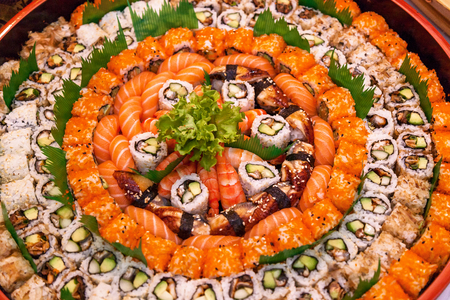 different types of sushi are stacked on a round dish Variety of japanese sushi rolls. Stock Photo