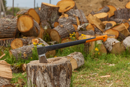 An ax in a wooden beam against the background of a pile of wooden firewood