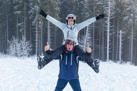 Young man holding his girlfriend on his shoulders. Girl embraces guy for neck. girl and guy in ski suits on vacation