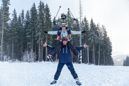 pyramid father mother and child in ski suits on vacation. Young man holding his girlfriend on his shoulders. Girl embraces guy for neck.