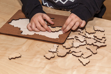 Man collects wooden puzzles on a wooden table Stock Photo