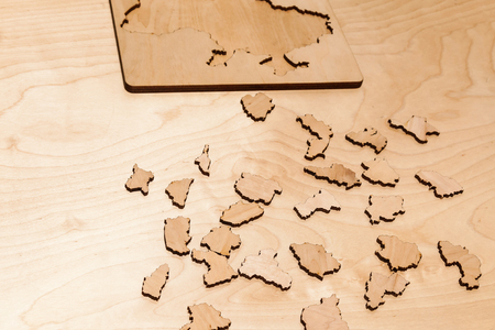 Wooden puzzles lie on a wooden table Stock Photo