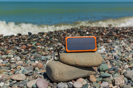 the poverbank lies on the pebbles by the sea and charges the phone. Powerbank charges the phone. Stock Photo