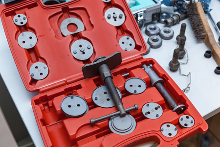 Special tool for mounting the caliper on the car, removable nozzles of different diameters in a red box. Stock Photo