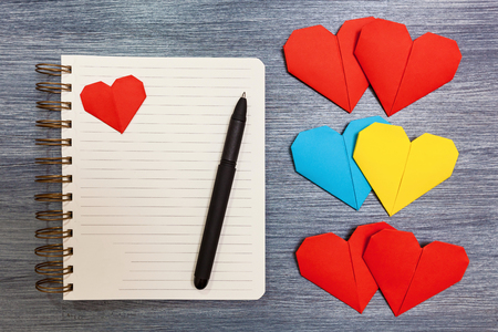 Notepad with multi-colored hearts and a pen lay on a table. Notepad with hearts.