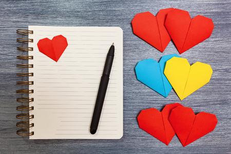 O bloco de notas com corações multi-colored e uma pena colocam em uma tabela. Bloco de notas com corações.