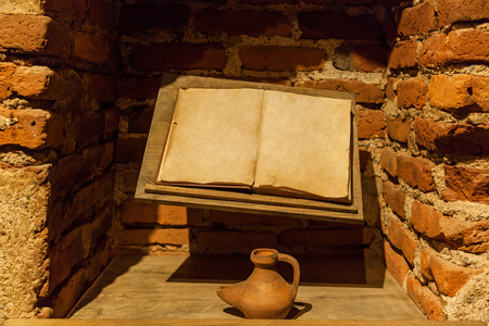 Ancient book with an inkwell near a brick wall. Ancient book with an inkwell. Stock Photo