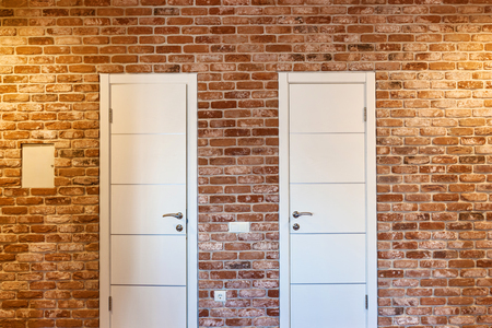 Two white doors in a brick wall. Two doors.