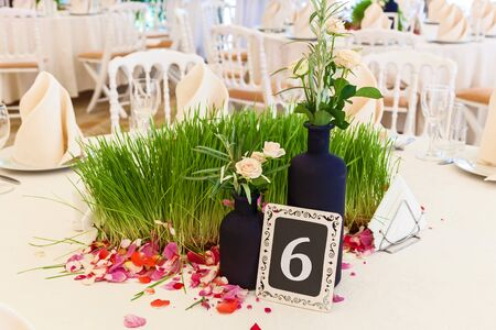 decor green grass and rose petals for the wedding table. Elegant wedding reception area, ready for guests and the bridal party.Table for guests in the wedding hall.