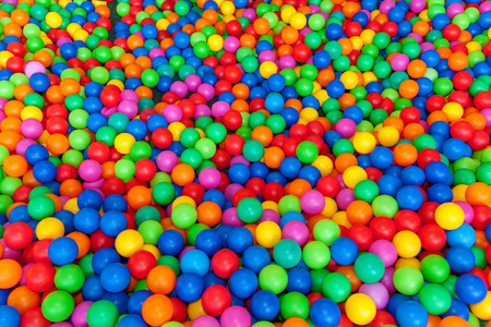 lots of colored balls in a playground ball pool.Ball with colorful plastic balls in children entertainment center. Pool with bright balls background.