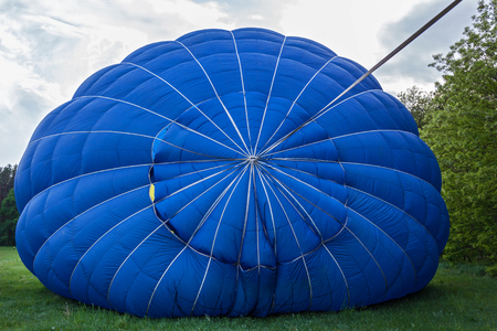 A balloon with a basket lies on the ground, equipment for filling the balloon with cold and hot air. Preparing the balloon for launch. Stock Photo