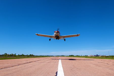The plane Piper Cherokee low flies over the runway. A small private airfield with different planes. Private aviation