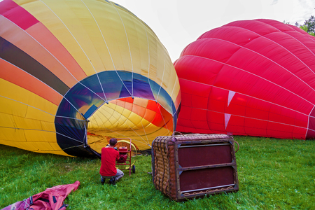 A balloon with a basket lies on the ground, equipment for filling the balloon with cold and hot air. Preparing the balloon for launch. Stock fotó