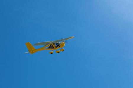 Light yellow aircraft flies in the blue sky