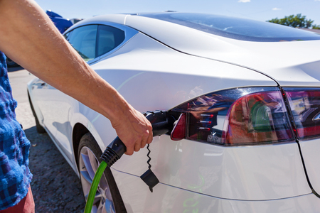Man inserts the charger into an electric vehicle. Electric vehicle charging station for home with EV car background