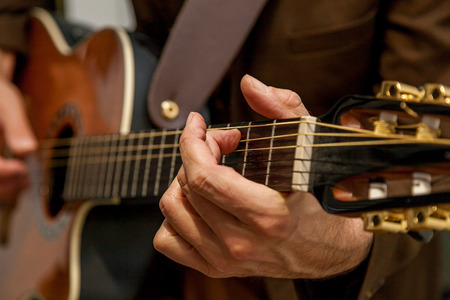 Close-up of the hands of a musician playing the guitar. The fingers of the musician are pressing the strings on the guitar. Musician playing bass guitar