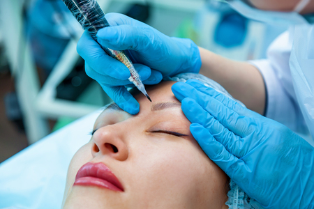 Beautician, applies a permanent makeup on the eyebrows. Eyebrow and lips tattoo Stok Fotoğraf