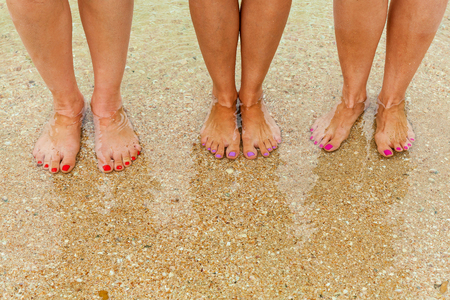 Female legs with multi-colored nails on the seabed are visible through the crystal clear water. Female feet in clear sea water, standing on small sea pebbles