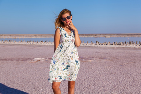 Beautiful sexy girl in white dress posing on a pink salt lake. Photo session tanned girl on a salty pink lake.