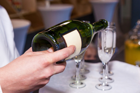 The waiter pours champagne into glasses from a bottle in a restaurant. Catering, banquet
