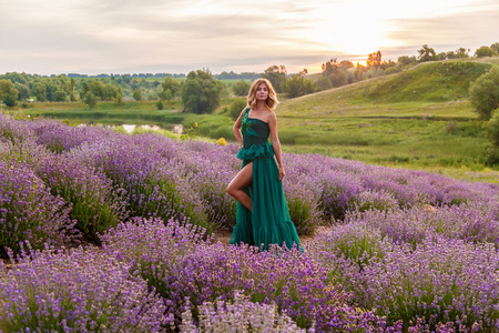 Beautiful girl in a green dress posing on a lavender field