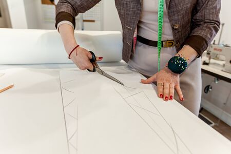 Womens hands cut the pattern out of paper with tailors scissors on a white table Stok Fotoğraf
