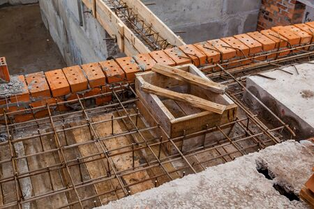 Metal structures for concrete structures. Construction site, tools, wheel barrow, sand and bricks at new house building, cement mixer machine and accessories