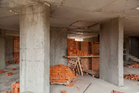 Walls of a multi-storey red brick house. Construction site, tools, wheel barrow, sand and bricks at new house building, cement mixer machine and accessories Фото со стока