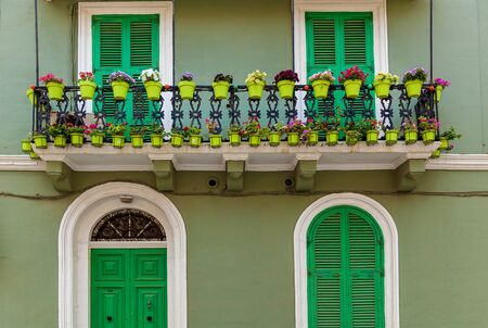 Malta architecture, facade of a house with wooden windows and a green balcony on the island of Malta