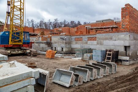 Construction site, tools, wheel barrow, sand and bricks at new house building, cement mixer machine and accessories Reklamní fotografie - 130004877