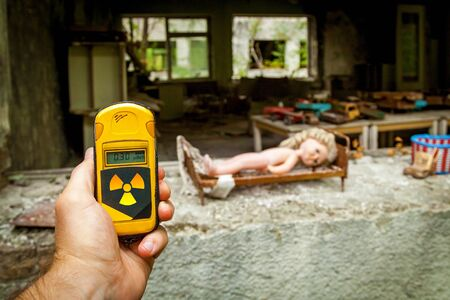 The dosimeter in the hands with the level of radioactivity in the abandoned building of the kindergarten after the explosion of the Pripyat reactor, Chernobyl.