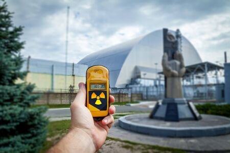 A dosimeter in hands with a level of radioactivity near the monument to the Chernobyl liquidators near the fourth reactor. Chernobyl disaster story. Lost place in Ukraine, USSR