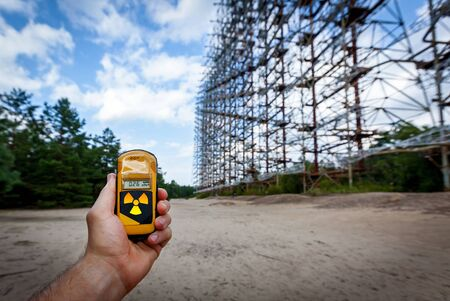 Dosimeter in hands with a level of radioactivity at 0.27 gamma radiation, the former military radar system Duga in the Chernobyl Exclusion Zone, Ukraine