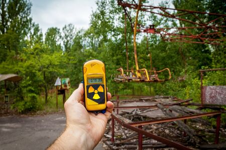 A dosimeter in hands with a level of radioactivity in an abandoned amusement park in the center of Pripyat, in the Chernobyl exclusion zone, Ukraine
