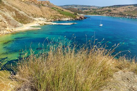 Maltese beach. Seashore of Malta. Ghajn tuffieha bay in summer. Tropical resort. Landscape with beach and clear sky.