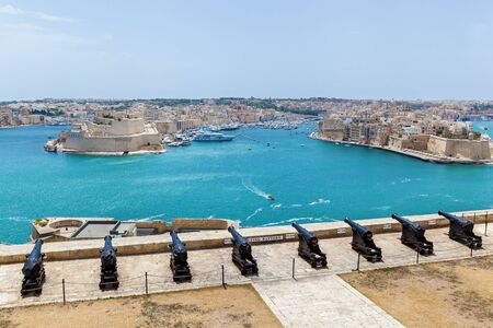 View of Vittoriosa harbor and the battery of medieval cannons from the wall of Valletta. Salyutovaya battery and the large Harbor of Valletta. View of the Grand Harbor from the Upper Gardens Barrakka in the capital of Malta, Valletta. Stock fotó