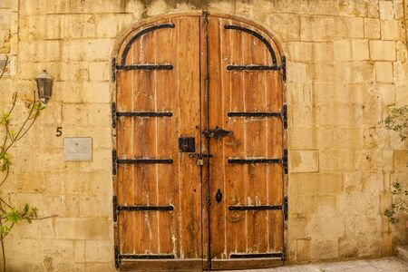 Texture of an old wooden wooden door with unusual metal handles on the island of Malta
