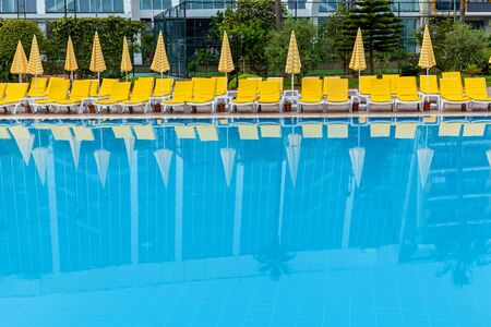 Blue swimming pool with yellow sun loungers and parasols for relaxing Stock fotó