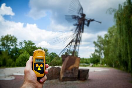 Dosimeter in hands with a level of radioactivity near the monument in memory of the Chernobyl accident. Chernobyl disaster story. Lost place in Ukraine, USSR