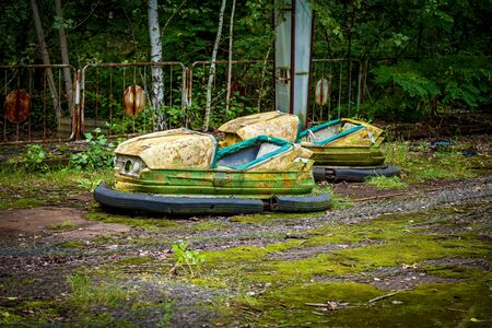Old broken children's electric cars in an amusement park, a recreation park in the city of Pripyat. Chernobyl nuclear power plant exclusion zone Stock fotó