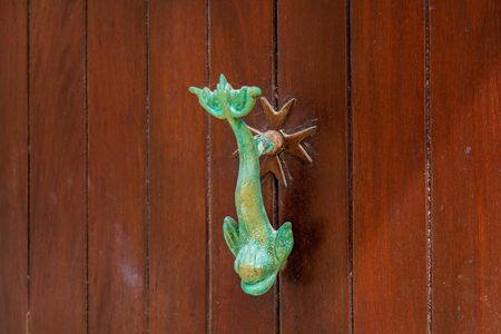Texture of an old wooden wooden door with metal handles in the form of a dolphin on the island of Malta Stock fotó