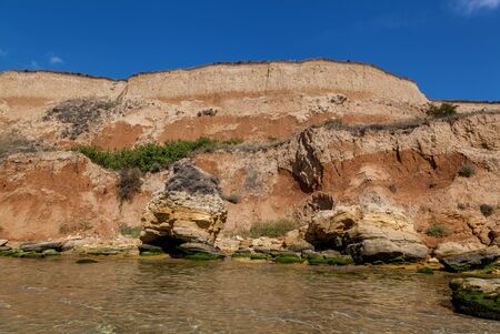 Yellow sandy rocks and stones of various forms on the Black Sea coast. Blue sky and turquoise water.